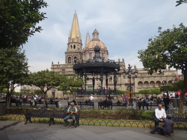 People relax on benches outside the cathedral.