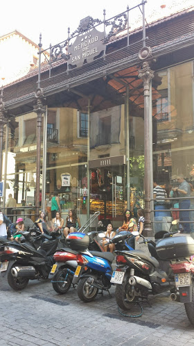 Motorcycles wait for their owners who are inside chowing down on high stools at counters inside Mercado San Miguel.