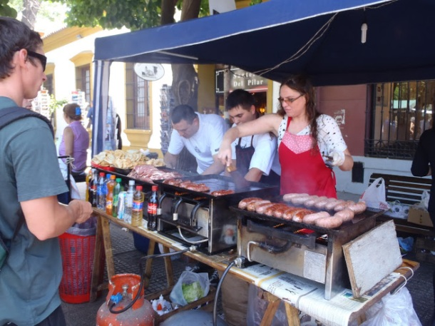 Choripan grilling on the street. Top them off with an ají marinade.
